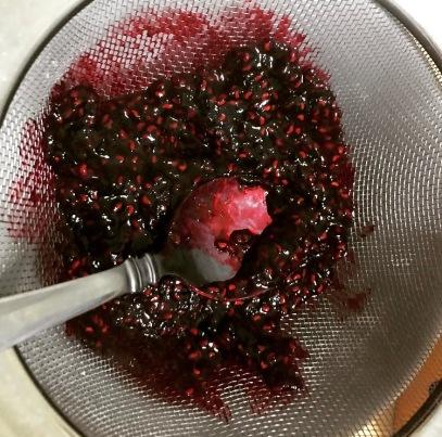 Pushing the raspberry sauce through the sieve